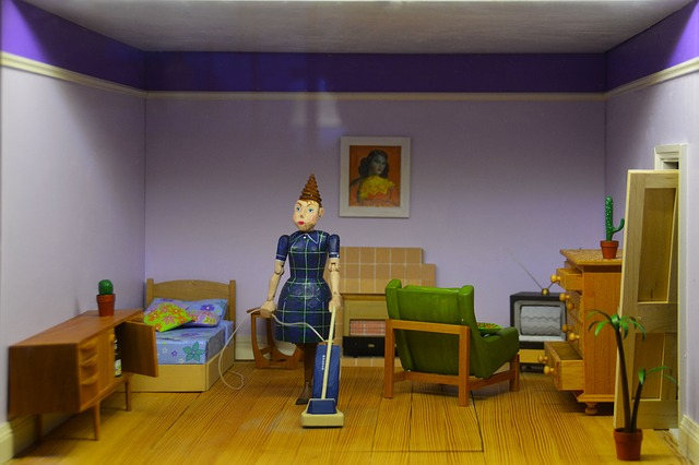 Doll vacuuming in a dollhouse