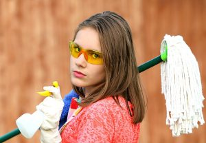 Girl looking unimpressed with cleaning supplies