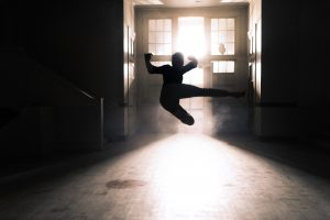 Backlit shadow of a person doing a flying kick