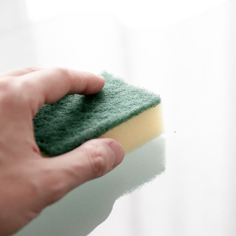A hand with a sponge, wiping a clean surface